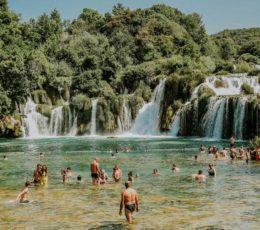people enjoying swimming by Krka waterfalls