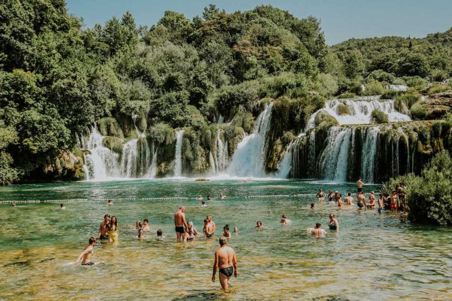 people enjoying swimming by Krka waterfalls